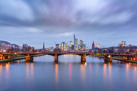 Schilderachtig uitzicht op de skyline van Frankfurt am Main en de brug van Ignatz Bubis Brucke tijdens het blauwe uur van de avond met spiegelreflecties in de rivier, Duitsland