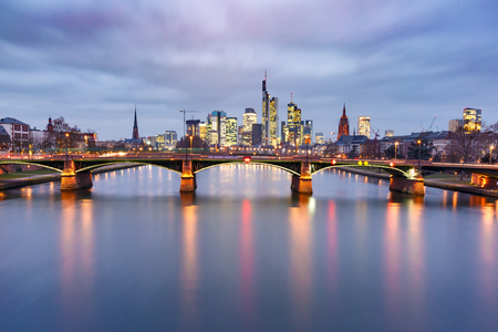 Picturesque view of Frankfurt am Main skyline and Ignatz Bubis Brucke bridge during evening blue hour with mirror reflections in the river, Germany Фото со стока