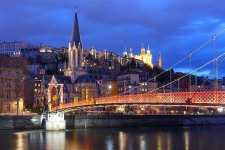 Panoramablick auf Saint Georges Kirche und Fußgängerbrücke über Saone Fluss, Altstadt mit Fourviere Kathedrale während der abendlichen blauen Stunde in Lyon, Frankreich