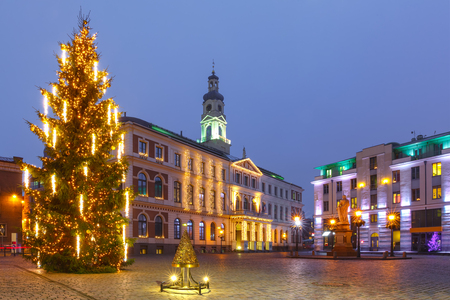City Hall Square with illuminated Christmas tree and Saint Roland Statue in Old Town of Riga at night, Latvia Stock Photo