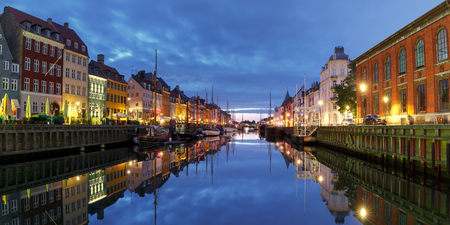 Panorama of Nyhavn with colorful facades of old houses and old ships in the Old Town of Copenhagen, capital of Denmark. Stock Photo