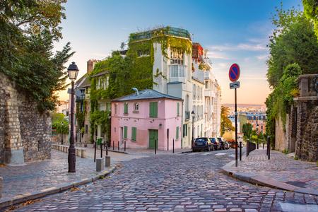Gemütliche alte Straße mit rosa Haus am sonnigen Sonnenaufgang, Viertel Montmartre in Paris, Frankreich