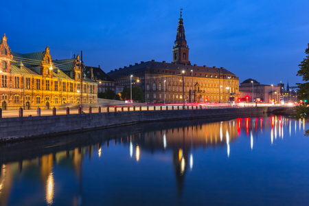 The Old Stock Exchange Boersen and Christiansborg Palace with their mirror reflection in canal at night, Copenhagen, capital of Denmark