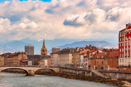 Scenic view of the banks of the Isere river and bridge, Collegiate Church of Saint-Andre with French Alps on the background, Grenoble, France