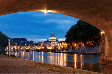Saint Peter Cathedral and Saint Angel bridge over the Tiber River during morning blue hour in Rome, Italy.