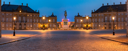 Statue of Frederick V at the centre of the Amalienborg Palace Square and Amalienborg Palace in Copenhagen, capital of Denmark. Panoramic night view.