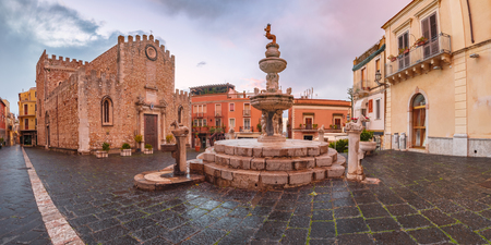 Cathedral of Taormina and fountain on the square Piazza Duomo in Taormina at rainy night, Sicily, Italy