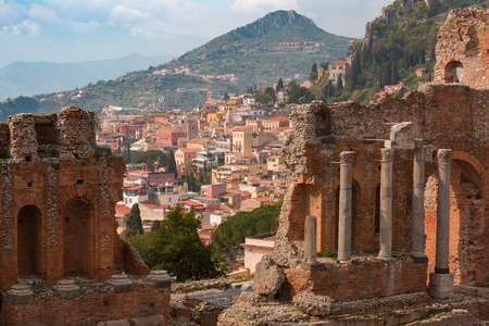 The Ruins of Ancient Greek theatre and Old Town of Taormina in sunny day, Sicily, Italy