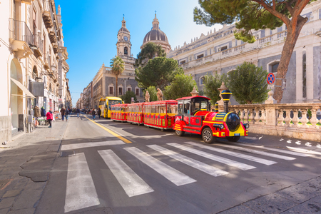 Tourist train near Cathedral of Santa Agatha on sunny morning, Sicily, Stock Photo