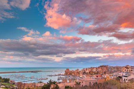Medieval fortress in Cala Marina, harbor in coastal city Castellammare del Golfo at sunset, Sicily, Italy