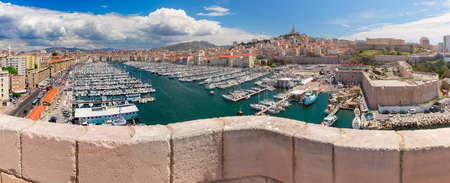 Panoramic view of sunny Old Port and the Basilica of Notre Dame de la Garde on the background, on the hill, Marseille, France