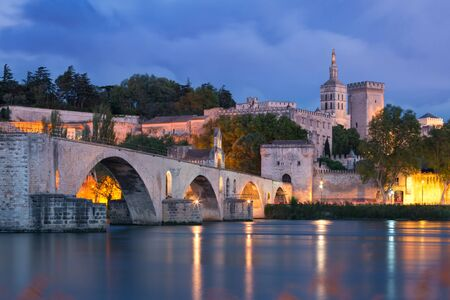 Famous medieval Saint Benezet bridge and Palace of the Popes during evening blue hour, Avignon, southern France