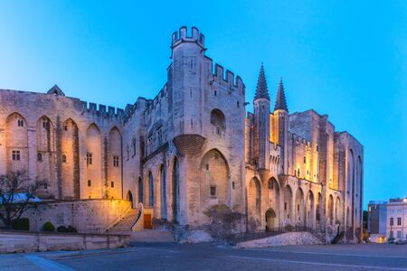 Palace of the Popes, once a fortress and palace, one of the largest and most important medieval Gothic buildings in Europe, during evening blue hour, Avignon, southern France Stock Photo
