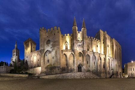 Palace of the Popes, once a fortress and palace, one of the largest and most important medieval Gothic buildings in Europe, during evening blue hour, Avignon, southern France