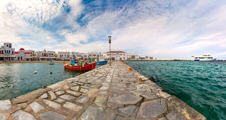 Pier with fishing boats, church and town hall in Old Port of Mykonos City, Chora, on the island Mykonos, Greece