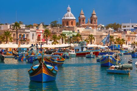 Traditional eyed colorful boats Luzzu and Parish Church of Our Lady of Pompei in the Harbor of Mediterranean fishing village Marsaxlokk, Malta Stock Photo