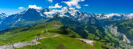 Hiking trail to summit of mountain Mannlichen, popular viewpoint in Swiss Alps, Switzerland. Eiger, Monch and Jungfrau, Lauterbrunnen in background.