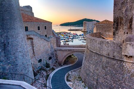 Old city walls and Old Harbour of Dubrovnik at sunset in Dubrovnik, Croatia