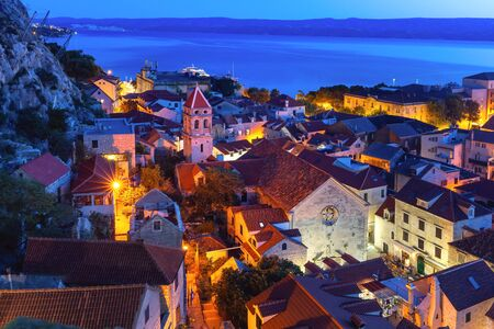 Red roofs of Old town and Church of St Michaelat night, Omis, popular tourist spot in Croatia