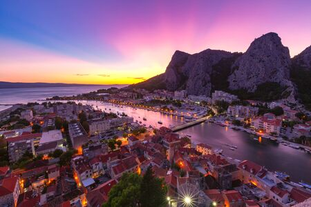 Beautiful aerial panoramic view of Cetina river, mountains and Old town at sunset, Omis, very popular tourist spot in Croatia