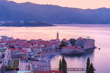 Aerial view over Old Town of Montenegrin town Budva on the Adriatic Sea at pink sunrise, Montenegro