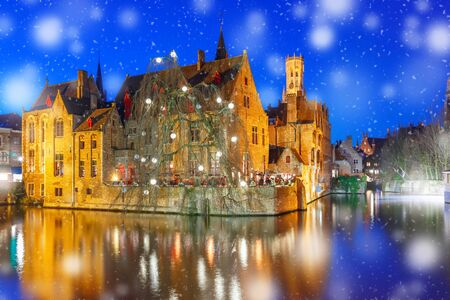 Medieval fairytale Old Town and tower Belfort from the quay Rosary, Rozenhoedkaai, in snowy evening, Bruges, Belgium