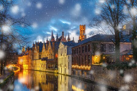Christmas night cityscape with a medieval tower Belfort and the Green canal, Groenerei, in Bruges, Belgium