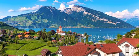 Aerial panoramic view of Spiez Church and Castle on the shore of Lake Thun in the Swiss canton of Bern at sunset, Spiez, Switzerland.