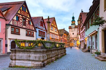 Decorated and illuminated Christmas street with gate and tower Markusturm in medieval Old Town of Rothenburg ob der Tauber, Bavaria, southern Germany