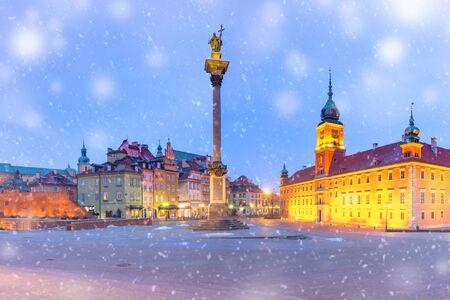 Schlossplatz mit Königsschloss, bunten Häusern und Sigismund-Säule in der Altstadt während der verschneiten blauen Morgenstunde, Warschau, Polen. Standard-Bild