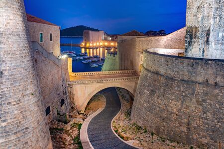 Old city walls and Old Harbour of Dubrovnik at night in Dubrovnik, Croatia