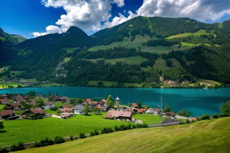 Swiss village Lungern with its traditional houses and old church tower Alter Kirchturm along the lake Lungerersee, canton of Obwalden, Switzerland