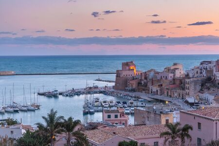 Medieval fortress in Cala Marina, harbor in coastal city Castellammare del Golfo at pink sunrise, Sicily, Italy