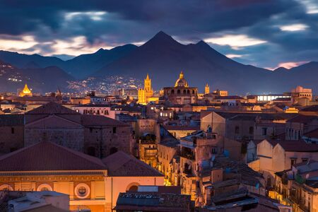 Aerial view of Palermo cathedral, mountains and rooftops of Old Town at night, Sicily, Italy