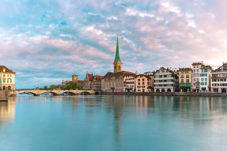 Famous Fraumunster church with its reflection in river Limmat at pink sunrise in Old Town of Zurich, the largest city in Switzerland Standard-Bild