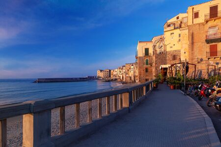 Tourist promenade and empty beach in old town of coastal city Cefalu at sunset, Sicily, Italy Standard-Bild