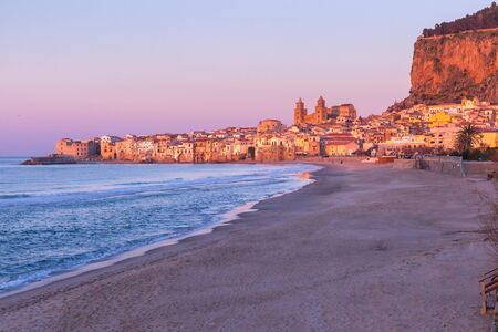 Beautiful view of empty beach, Cefalu Cathedral and old town of coastal city Cefalu at pink sunset, Sicily, Italy