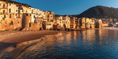 Beautiful panorama of the beach and old town of coastal city Cefalu at sunset, Sicily, Italy