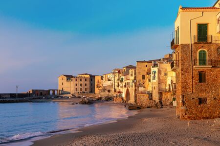 Empty sand beach in old town of coastal city Cefalu at sunset, Sicily, Italy