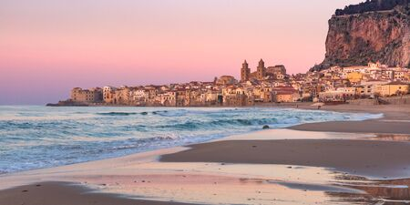 Beautiful view of sand beach, Cefalu Cathedral and old town of coastal city Cefalu at sunset, Sicily, Italy Standard-Bild