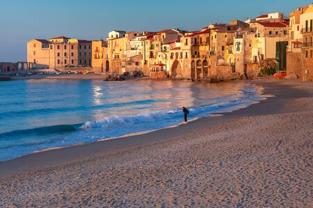 Sunny sand beach in old town of coastal city Cefalu at sunset, Sicily, Italy Standard-Bild