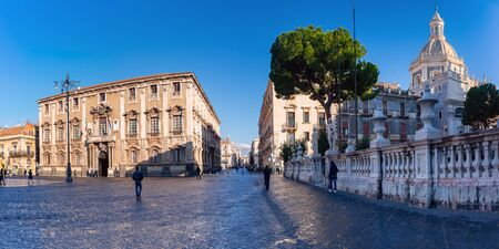 The first sunray on Via Etnea and Piazza Duomo with the Cathedral of Santa Agatha and town hall at sunrise, Catania, Sicily,