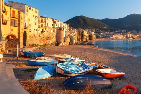 Boats on the beach and sunny houses in coastal city Cefalu at sunset, Sicily, Italy