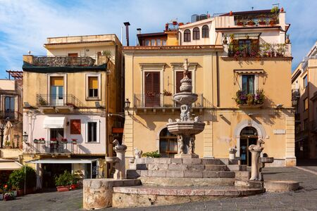 Fountain and typical houses with restaurants on the square Piazza Duomo in Taormina on sunny morning, Sicily, Italy