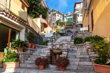 Colorful narrow stairs street with Fountain and flowers near square Piazza Duomo in Taormina in sunny morning, Sicily, Italy Standard-Bild