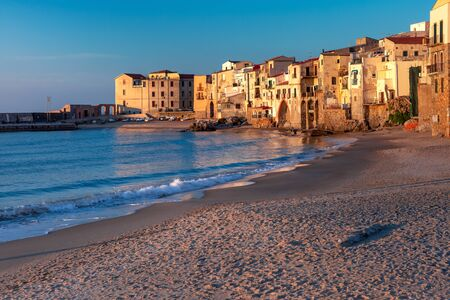 Beautiful view of empty sunny sand beach and old town of coastal city Cefalu at sunset, Sicily, Italy