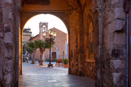 Empty Corso Umberto street and Piazza 9 Aprile square in rainy morning, view from Porta di Mezzo, Old Clock Tower and gateway, Taormina, Sicily, Italy Editorial