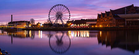 Panorama of Motlawa River and Ferris wheel with water reflection in Old Town of Gdansk at night, Poland Banque d'images