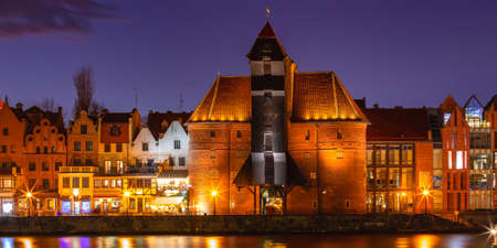 Old harbour crane and city gate Zuraw in old town of Gdansk at night, Poland