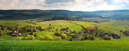 Rural landscape with picturesque village Volovets at sunset with green fields and hills in Carpathian Mountains